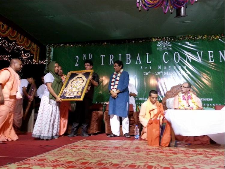 Un invitado tribal se presenta con una imagen del Señor Nrsimhadeva