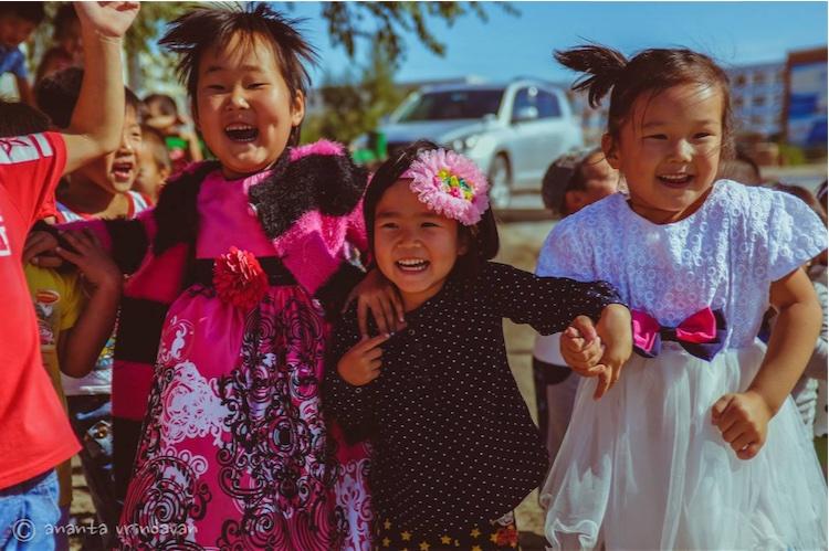 Los chicos locales felices de bailar y cantar con los devotos Hare Krishna